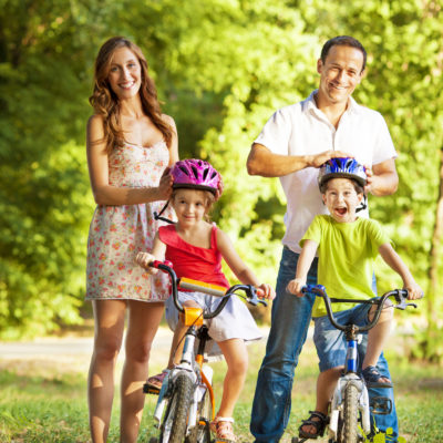 Young happy family having a break after riding bicycles in a park. Posing for family portrait.