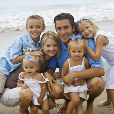 A beautiful, young family gathers together on the beach for a family portrait
